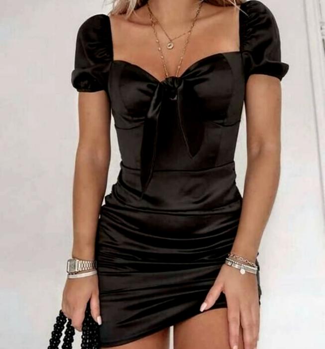 chica rubia usando un vestido negro de manga corta, de satén con escote cuadrado y moño al frente