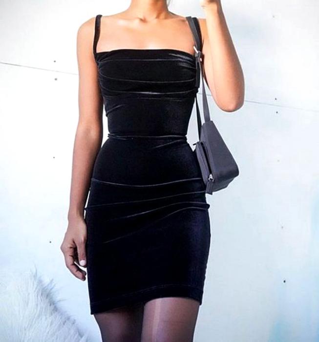 chica usando vestido de terciopelo negro de tirantes, ceñido al cuerpo con medias semitransparentes y bolso de mano gris