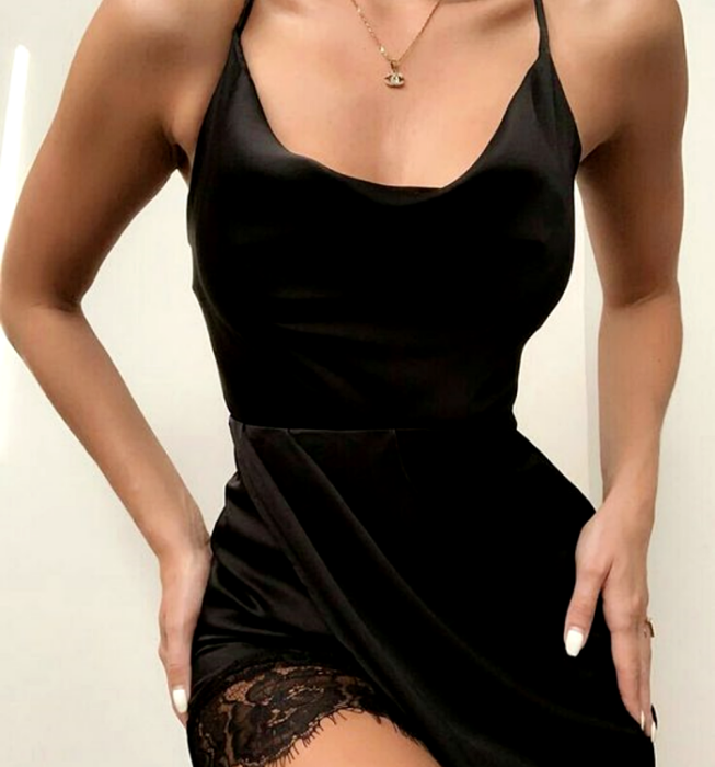chica usando vestido negro de satén de tirantes con vista de encaje negro en la pierna