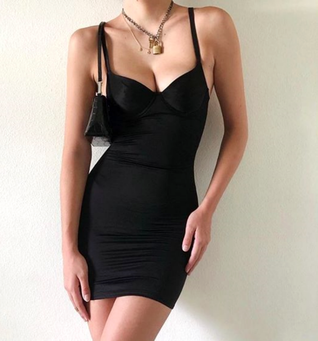 girl wearing a short black dress with straps with V-neckline and close to the body
