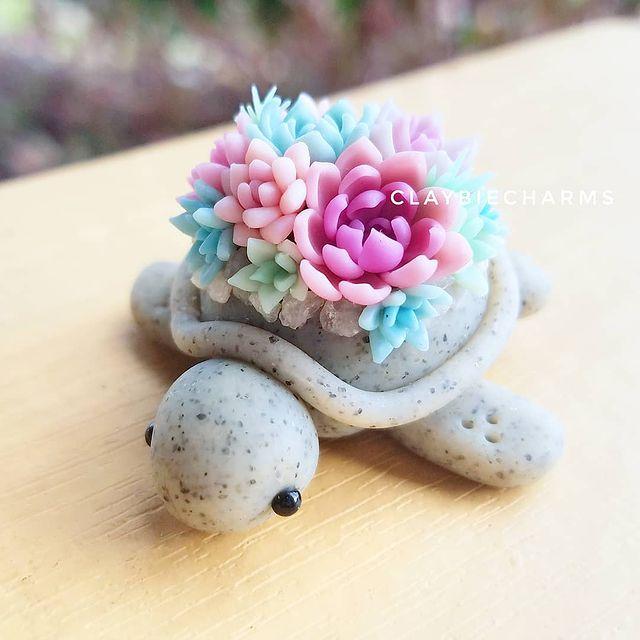 Tortuga gris con suculentas rosas, lilas y azules hecha con arcilla polimérica