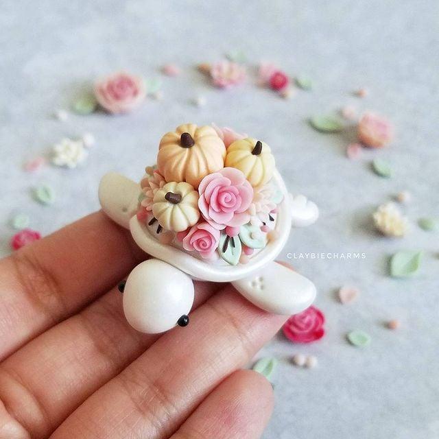 Tortuguita blanca con calabazas y rosas en el caparazón hecha de arcilla polimérica