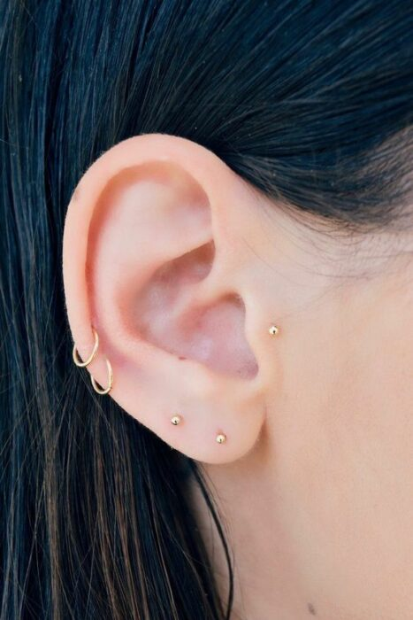 Girl with rings and buckles in her ear; 13 Creative Ways to Wear More Than One Ear Piercing