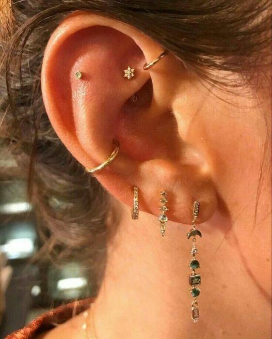 chica con multiples pendientes en el oído; 13 Creativas maneras de llevar más de un piercing en el oído