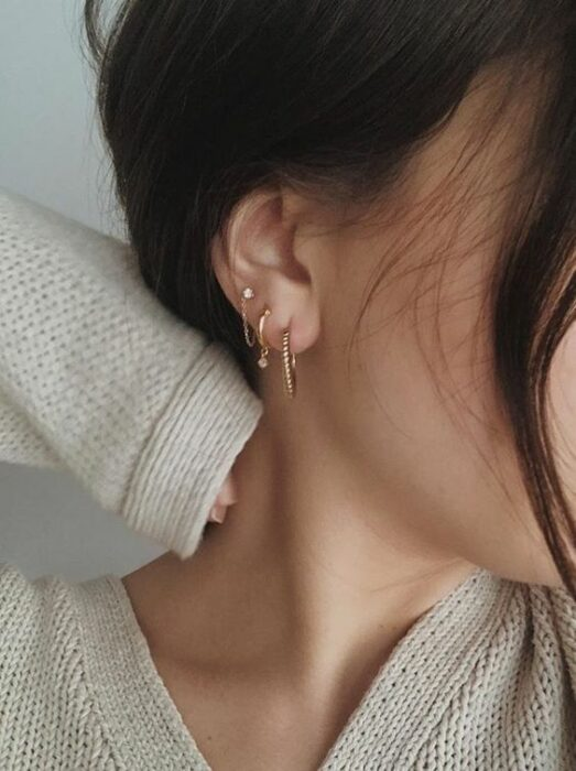 Girl with three rings in ear; 13 Creative Ways to Wear More Than One Ear Piercing