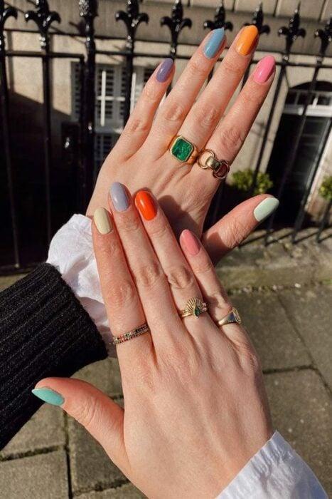 Chica mostrando su manicura en colores vibrantes; 19 Manicuras estilo arcoíris a las que no te podrás negar