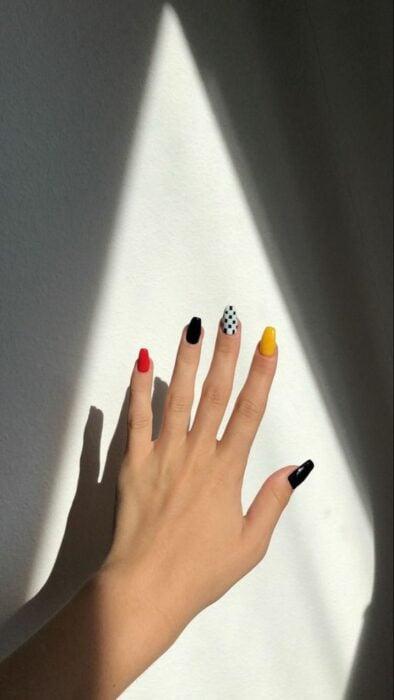 Chica con manicura en tonos rojo, amarillo, negro y blanco; 19 Manicuras estilo arcoíris a las que no te podrás negar