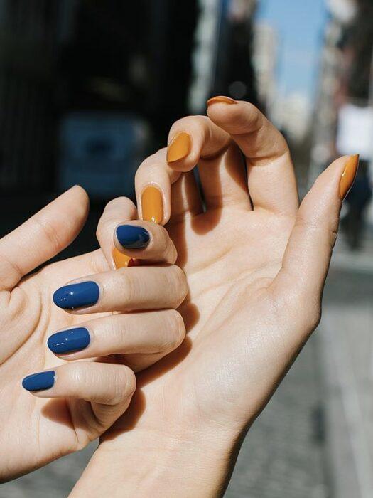 Chica con manicura de doble color en azul y mostaza; 19 Manicuras estilo arcoíris a las que no te podrás negar