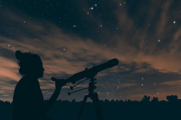 Chica viendo por el telescopio las estrellas