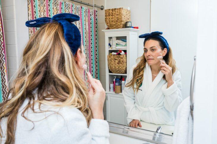 Mujer embarazada utilizando su rodillo de jade en el rostro frente al espejo