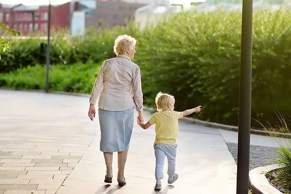 Abuela camina con su nieto pequeño de la mano