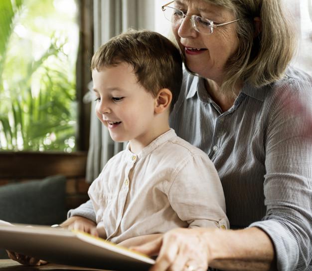 Abuela y nieto leen un libro juntos