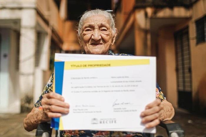 Abuelita sonriendo mostrando las escrituras de su casa