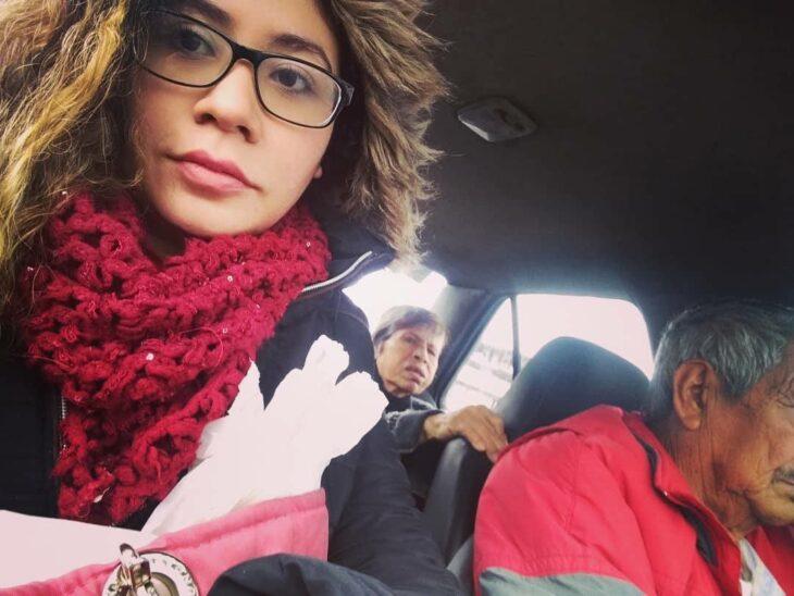 Chica con lentes, cabello suelto y bufanda roja toma foto en un taxi con dos ancianitos