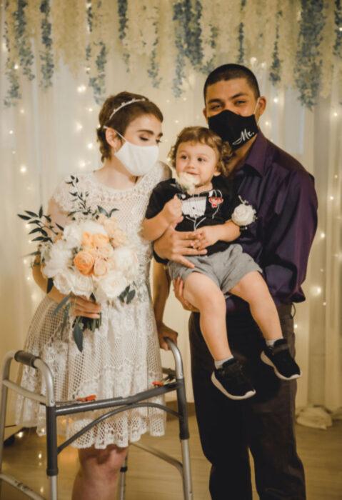 Pareja se casa en hospital gracias a enfermeras; esposos recién casados con bebé en brazos; mujer de cabello corto y castaño pelirrojo, con vestido blanco de encaje y ramo de flores, bebé rubio chino, hombre con cabello rapado, pantalón de vestir y camisa morada