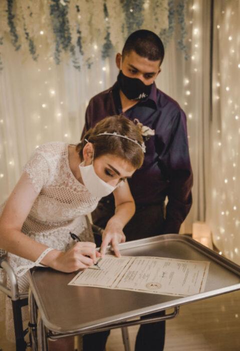 Pareja se casa en hospital gracias a enfermeras; esposos recién casados firmando acta de matrimonio, mujer de cabello corto, castaño pelirrojo, con vestido blanco de encaje, hombre con cabello rapado y camisa morada de vestid