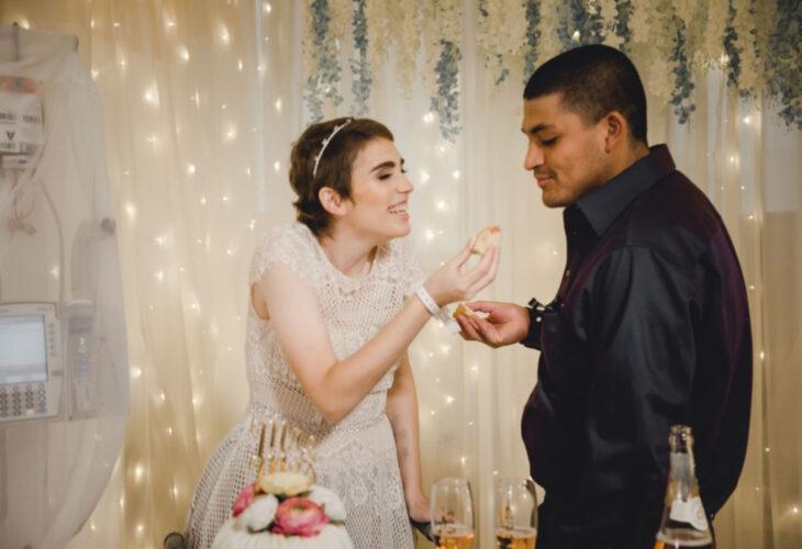 Pareja se casa en hospital gracias a enfermeras; esposos recién casados comiendo pastel de bodas, mujer de cabello corto y pelirrojo, con vestido blanco de encaje, sonriendo, hombre de cabello rapado con camisa morada de satín de vestir