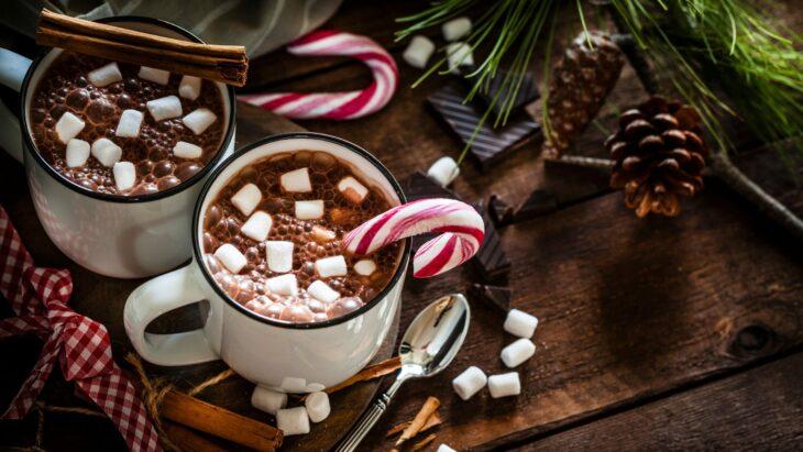 Taza de chocolate oscuro decorado con bombones y un bastón de caramelo