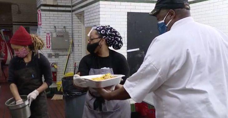 Grupo de cocineros cargando una tarja de metal con papas asadas