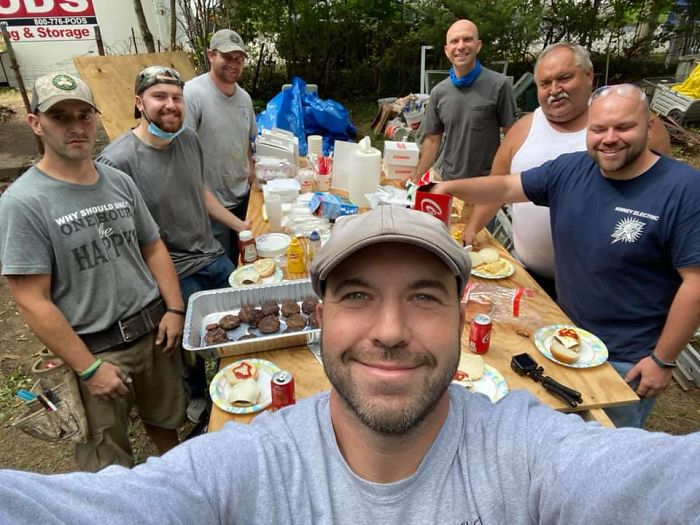 John Kinney tomando una selfie con un grupo de constructores detrás de él al rededor de una mesa rectangular de madera con comida encima