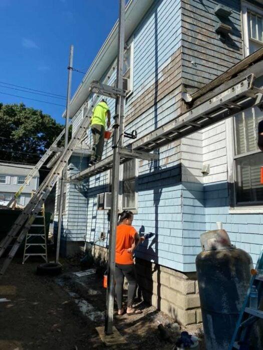 Dos personas con playeras verde neón y naranja pintando y reparando una casa de dos pisos color azul cielo