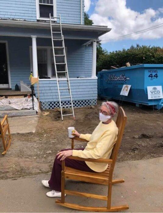 Anciana vistiendo suéter amarillo y pantalón guinda sentada en una mecedora de madera sosteniendo un vaso blanco con la mano derecha con una casa de dos pisos en el fondo color azul