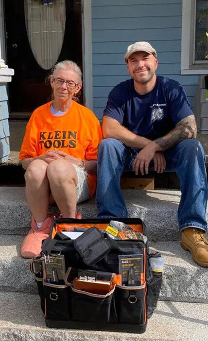 John Kinney con Gloria Scott sentados en los escalones de una casa color azul con una maleta de herramientas negras en el piso
