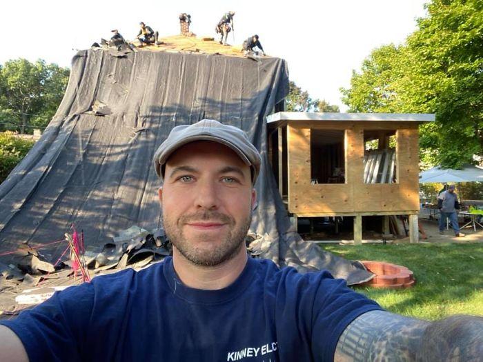 John Kinney tomando una selfie vistiendo una blusa azul marino y de fondo la reparación de una casa
