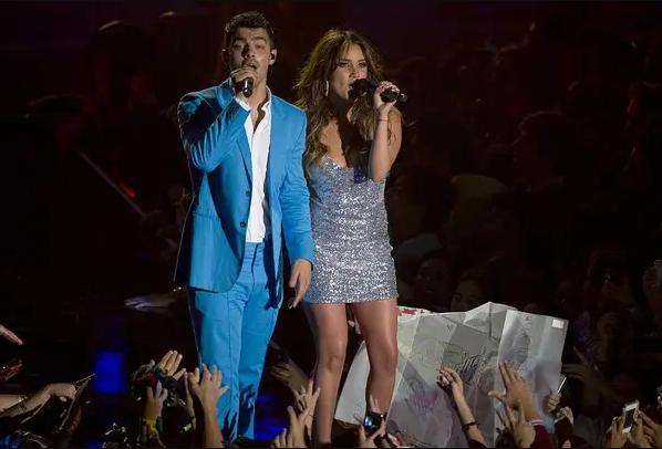 Joe Jonas con Dulce María cantando