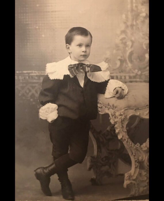 Foto vintage, fotografía antigua color blanco y negro de niño con traje antiguo, traje con holanes y botas