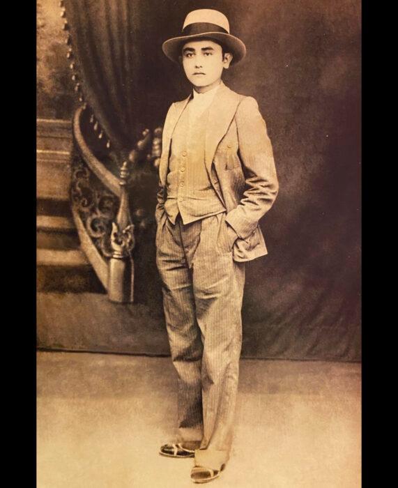 Foto vintage, fotografía antigua en color sepia de joven con traje elegante, sombrero, camisa, chaleco, saco, pantalones de vestir, con las manos en las bolsas