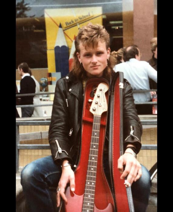 Foto vintage, fotografía antigua a color, de hombre rockero de cabello corto de arriba y largo de abajo, rubio, con bajo, chamarra de cuero negra