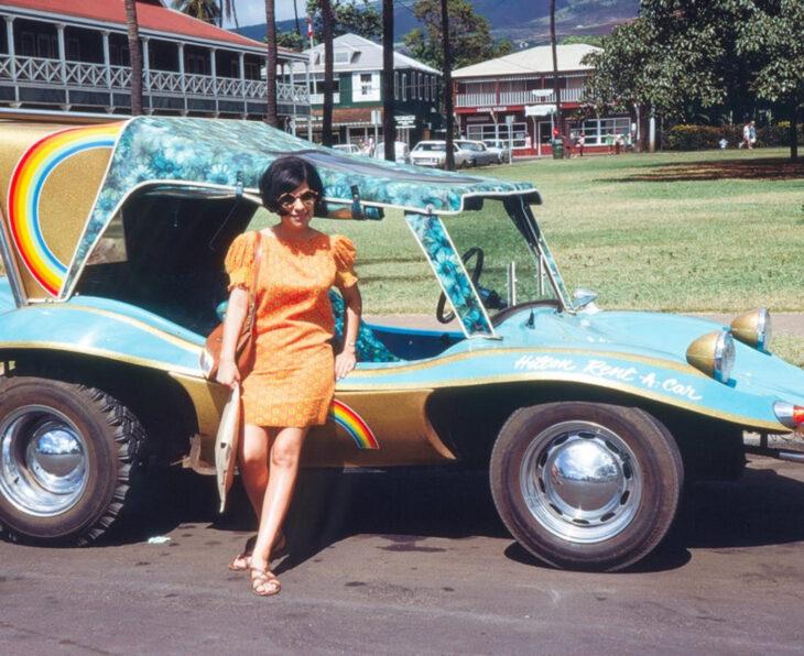 Foto vintage, fotografía antigua a color de mujer con cabello negro, corto, vestido anaranjado, lentes de sol, sandalias, recargada en un auto antiguo azul