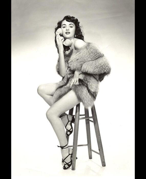 Foto vintage, fotografía antigua en blanco y negro de mujer estilo pinuo sentada en un banco con teléfono antiguo en la mano