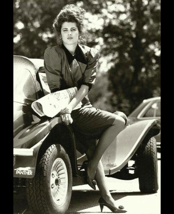 Foto vintage, fotografía antigua en color sepia, mujer con vestido de puntos recargada en un auto vintage