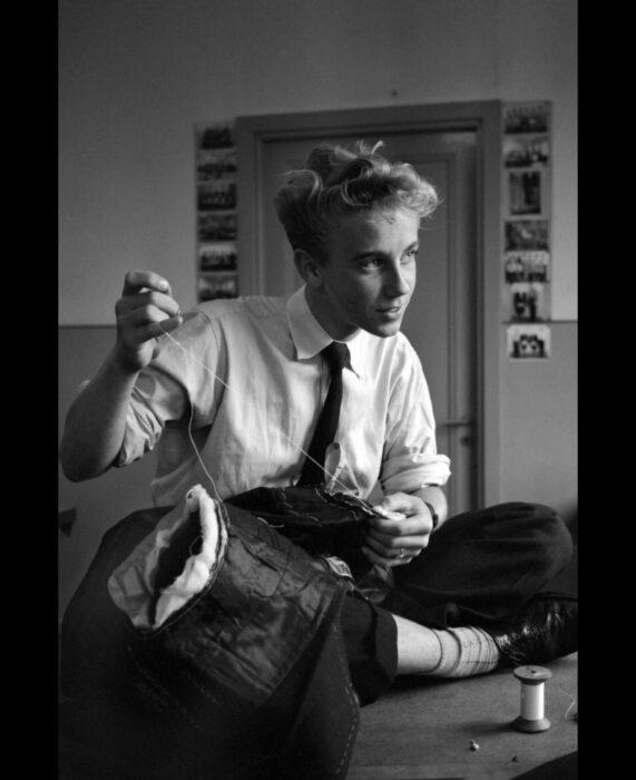 Foto vintage, fotografía antigua de hombre guapo sentado en una mesa cosiendo ropa, vestido con camisa blanca, corbata, pantalones de vestir y zapatos