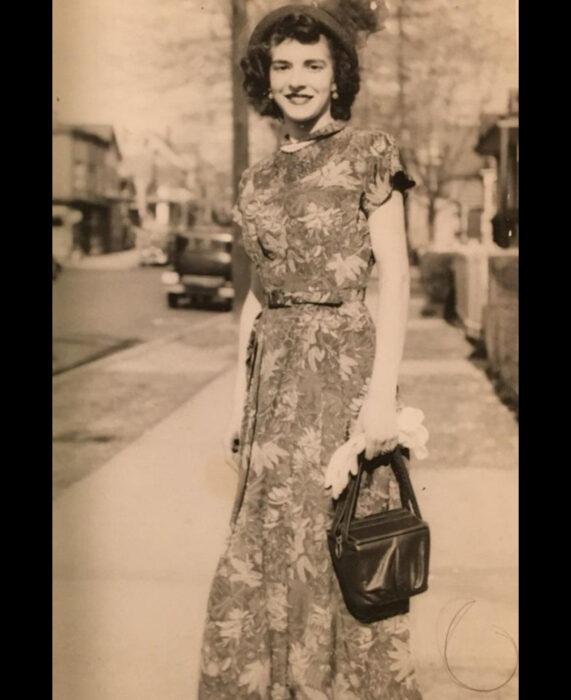 Foto vintage, fotografía antigua color sepia de mujer en la calle, con cabello corto y chino, sombrero, vestido largo de flores y bolsa negra