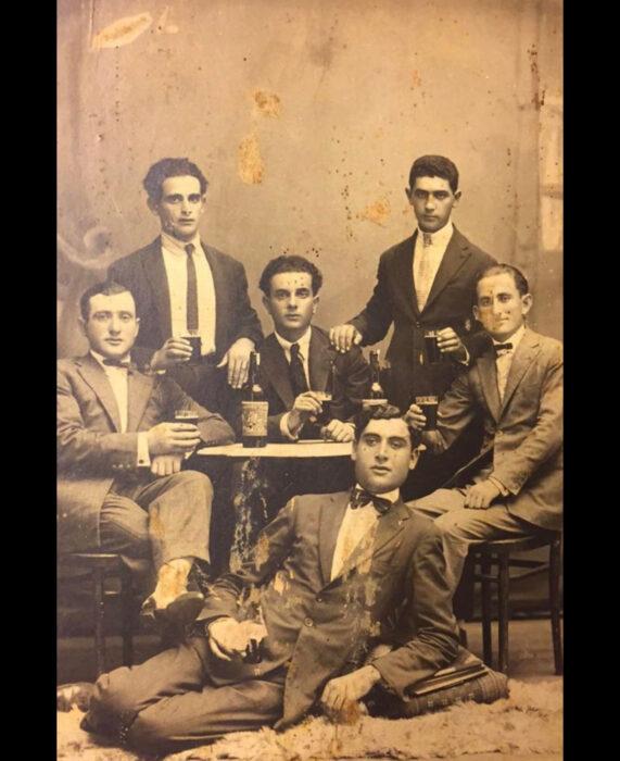Foto vintage, fotografía antigua en color sepia de hombres con traje sentados en una mesa bebiendo