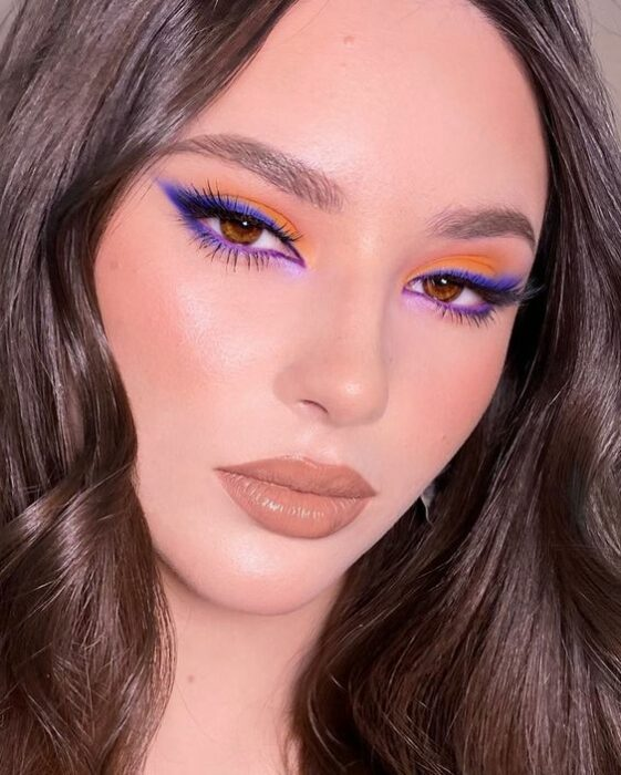 Chica blanca de cabello castaño suelto ondulado con maquillaje foxy eye color morado con naranjas y labios nude