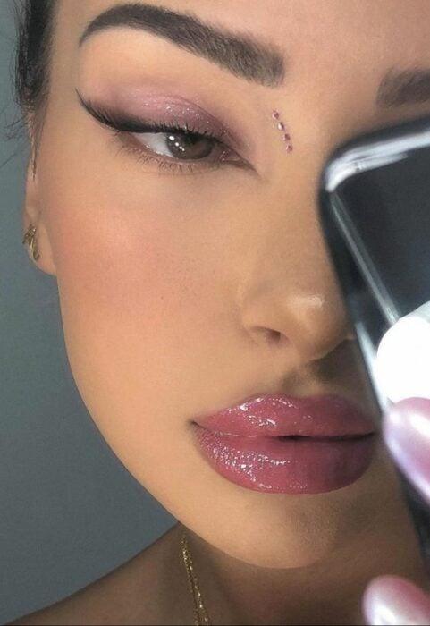 Chica morena con labios carnosos color rosas con gloss y maquillaje de ojos foxy eyes