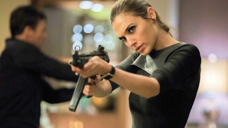 Escena de película en la que aparece Gal Gadot sosteniendo un arma de fuego