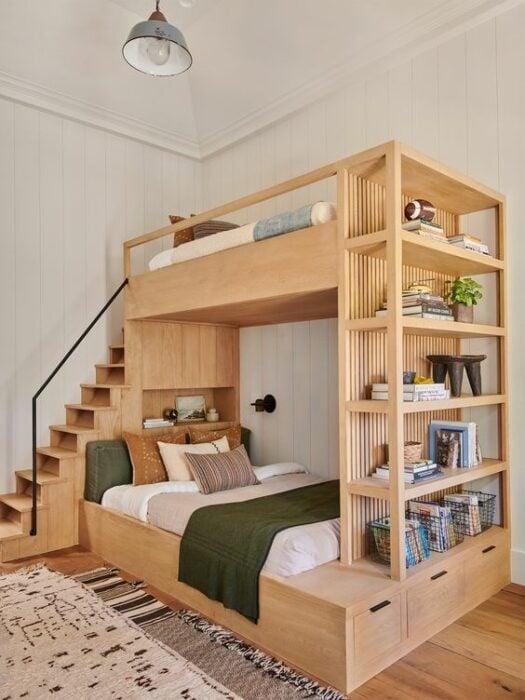 Mueble para cama de dos pisos color madera con cama matrimonial en la parte de abajo con cobijas claras y cobijes naranjas y unos escalones para subir a la planta alta