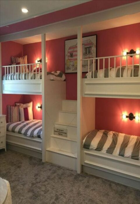 Habitación con paredes color rosas y alfombra gris con cuatro camas pegadas  la pared con mueble blancos y unos escalones para subir a la parte de arriba