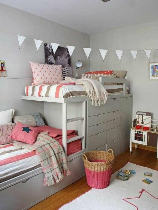 Habitación blanca con muebles grande para cama de dos pisos con cajones para guardar ropa y camas con cobijas blancas con rayas cafés y rosas