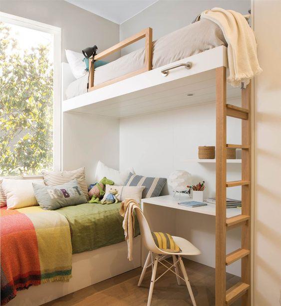 Habitación blanca con cama de planta alta con cama de cobija verde y mucho cobijes en la plata de abajo junto a un escritorio blanco y unas escaleras de madera a un lado para subir a la parte de arriba