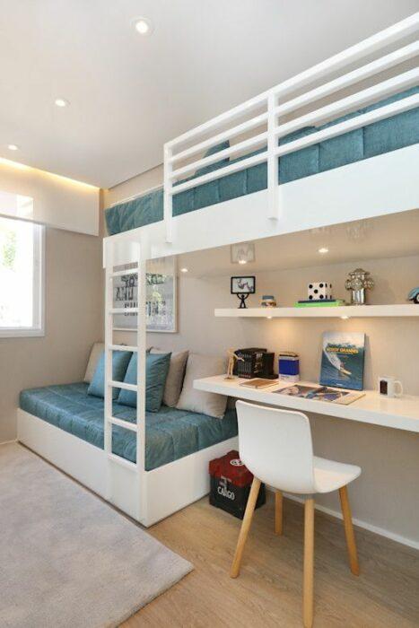 Habitación blanca con piso de madera y una alfombra gris con un mueble grande para cama de dos plantas color blanco y camas con cobijas azules