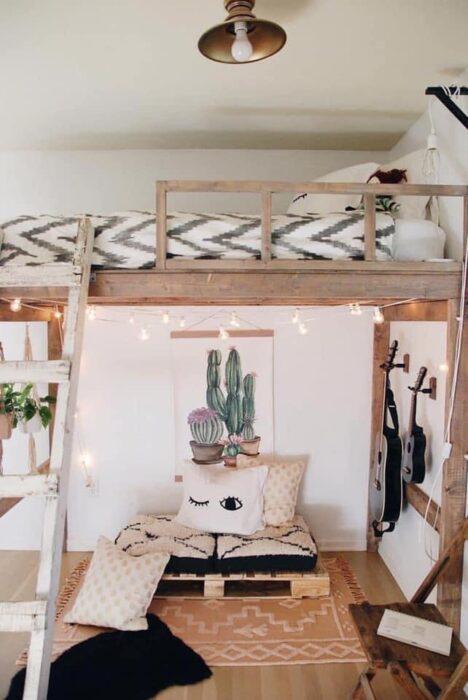 Habitación estilo bohemia con pared blanca y muebles de madera para cama alta con cobija blanca con figuras grises y en la parte de abajo un sillón hecho con palets y una alfombra beige