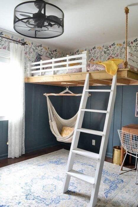 Habitación con pared azul y ventana con cortinas blancas con una cama de planta alta en color blanco y en la parte abajo una hamaca para sentarse con una cojín amarillo
