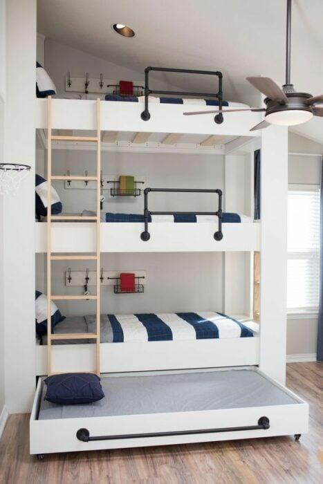 Cama de tres pisos con mueble color blanco y escaleras beige con cobijas  blancas con rayas azul marino