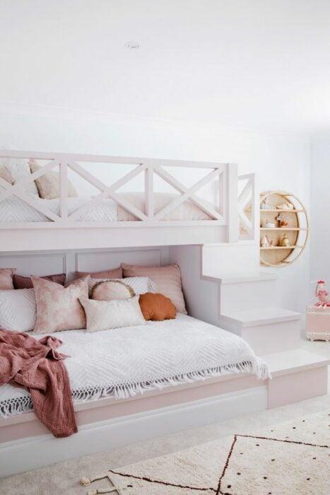 Habitación blanca con cama de dos pisos blanca y escalones para subir a la planta alta